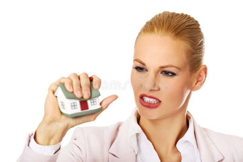 Aggressive Geschäftsfrau, die kleines Haus zerquetscht stockfotografie