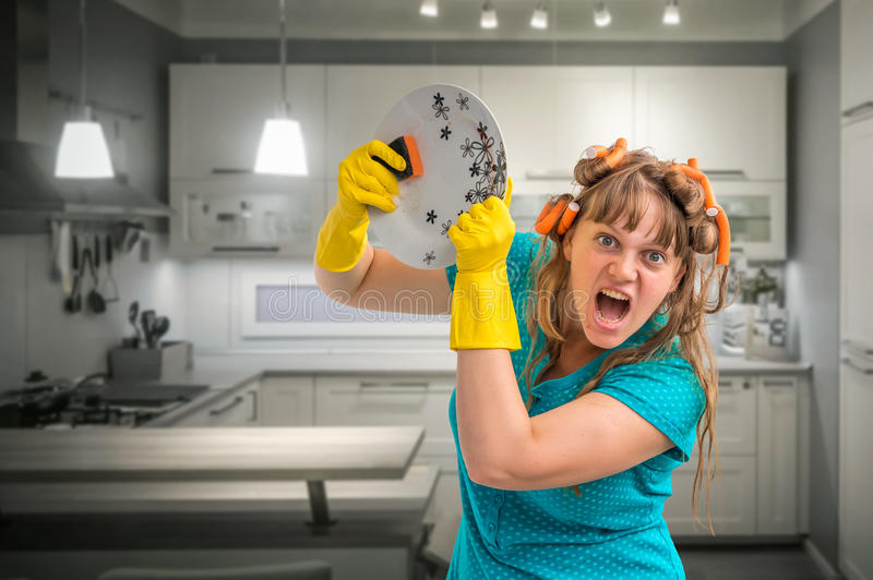 Aggressive housewife woman washing dishes in kitchen stock image