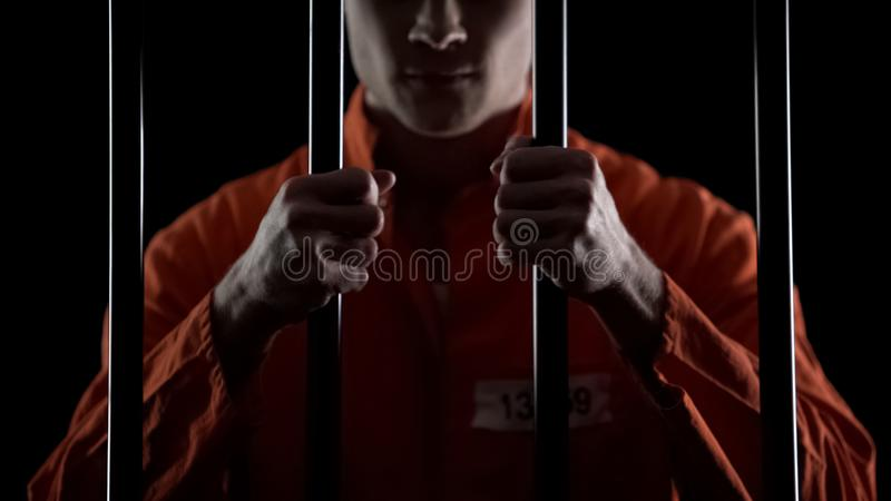 Aggressive inmate holding prison bars, unfairly judged, court sentence appeal. Stock photo stock photos