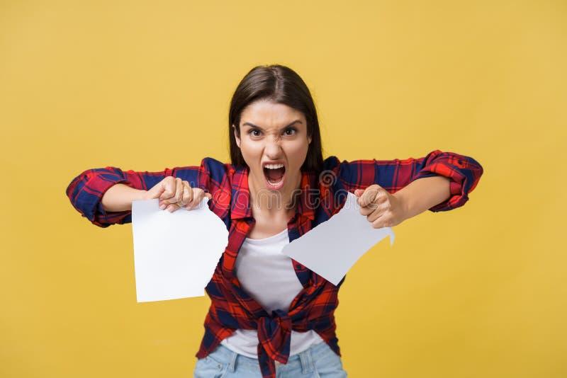 Aggressive junge kaukasische Frau zerreißt Vertrag oder weißes Blatt Papier Lokalisiert über gelbem Hintergrund stockfoto
