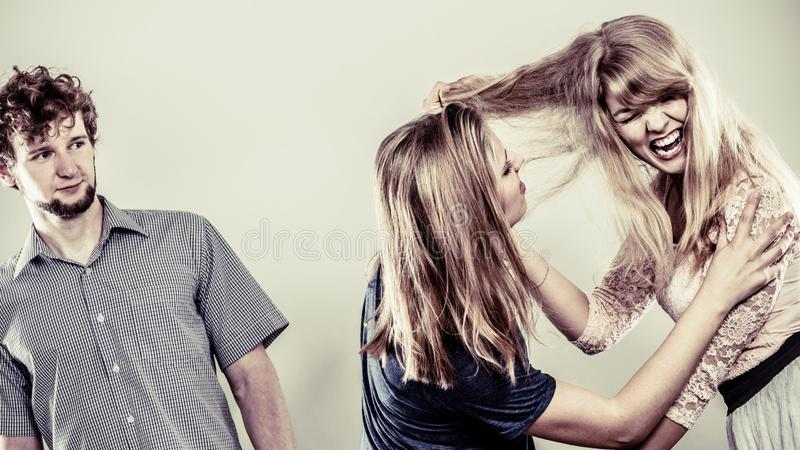 Aggressive mad women fighting over man royalty free stock images