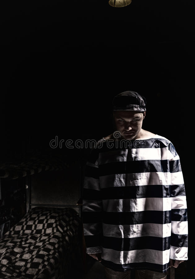 Aggressive male prisoner standing near his bed in a small dark p royalty free stock image