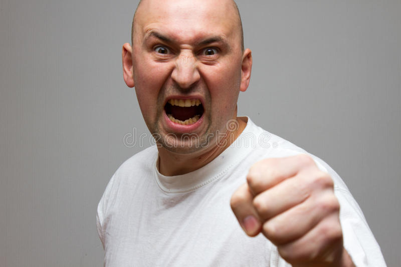 Aggressive man, holding his fist up on black background stock images