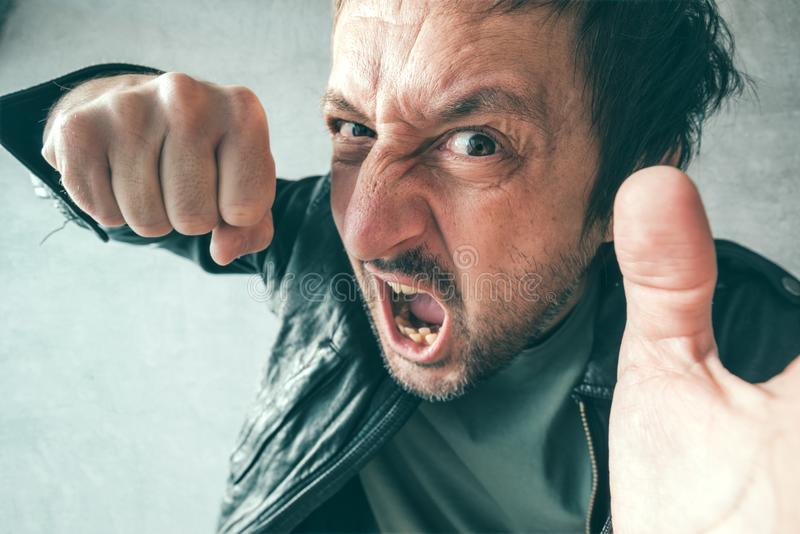 Aggressive man punching with fist, victim`s pov royalty free stock images