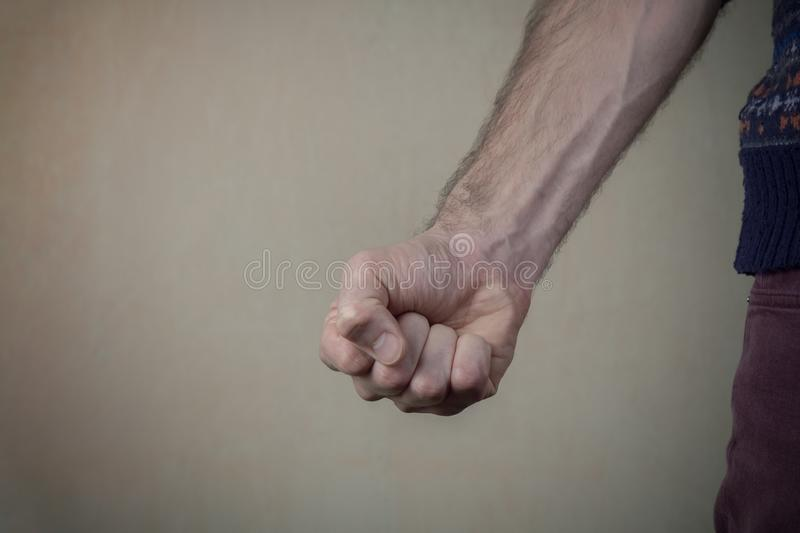Aggressive man threatens with clenched fist. Violence and aggression concept stock image