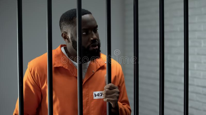 Aggressive prisoner holding bars and waiting for guard, inadequate criminal. Stock photo royalty free stock photo
