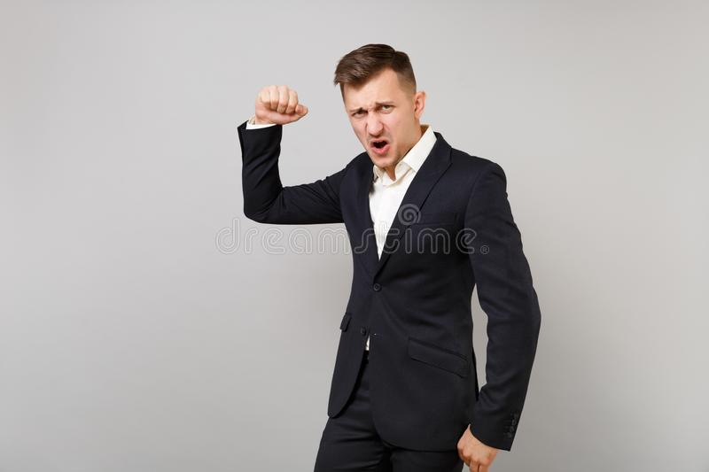 Aggressive young business man in classic black suit, shirt clenching fist, showing biceps muscles isolated on grey stock photos