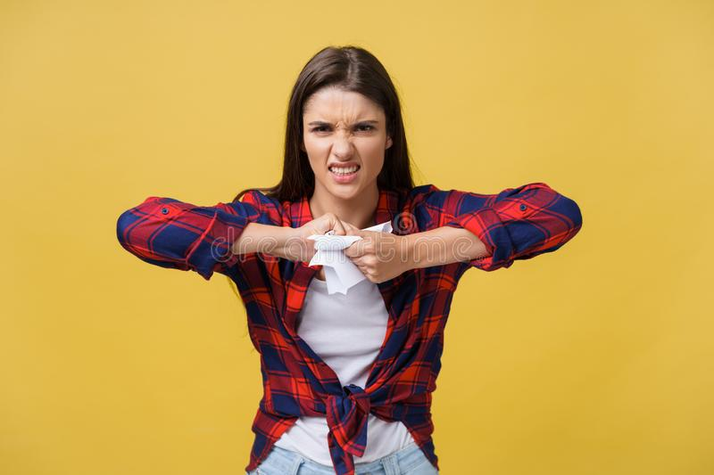 Aggressive young caucasian woman tears contract or white sheet of paper. Isolated over yellow background. Aggressive young caucasian woman tears contract or stock photo