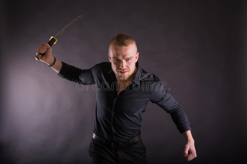 Aggressive young man holding katana sword Looking at the Camera.Against Wall Background stock photo