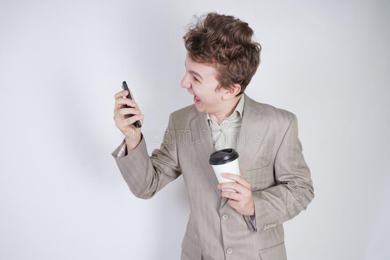 Aggressiver kaukasischer Jugendlicher schreit in das intelligente Telefon und hält einen Papiertasse kaffee in seiner Hand Studen stockbilder