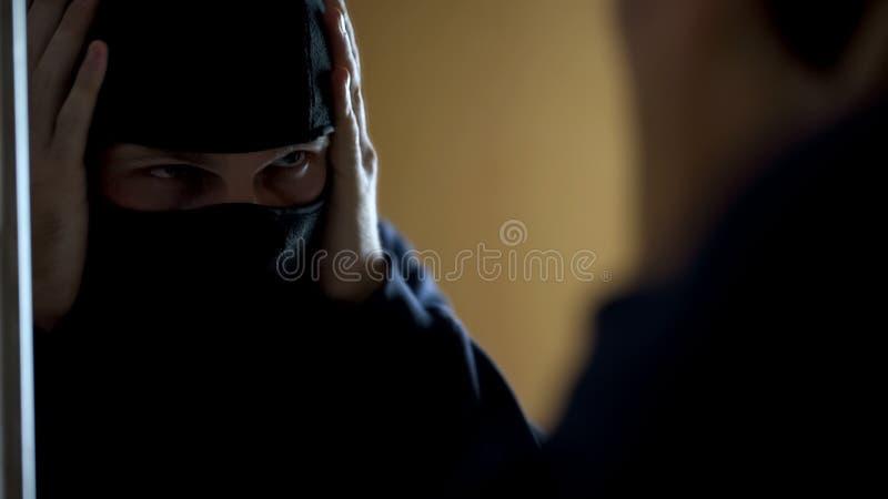 Aggressivt brottsligt sätta på balaclavaen framme av spegeln för röveri royaltyfri foto