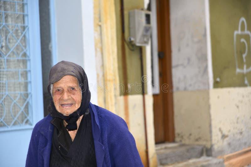 Agiassos Lesvos October21 2015 La donna greca sta camminando nel suo villaggio greco tipico fotografia stock libera da diritti