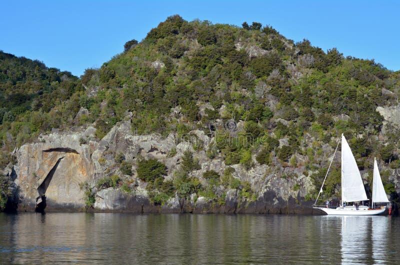 Żagiel łódź blisko Maoryjskiego Rockowego cyzelowania przy jeziornym Taupo Nowa Zelandia fotografia stock