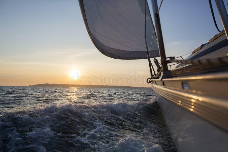 Żagiel łodzi żeglowanie W morzu Podczas zmierzchu zdjęcie royalty free