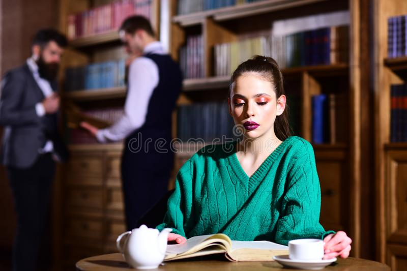 Agile business and grammar concept. woman in library read book at teapot drinking coffee from cup. literature cafe with royalty free stock photos