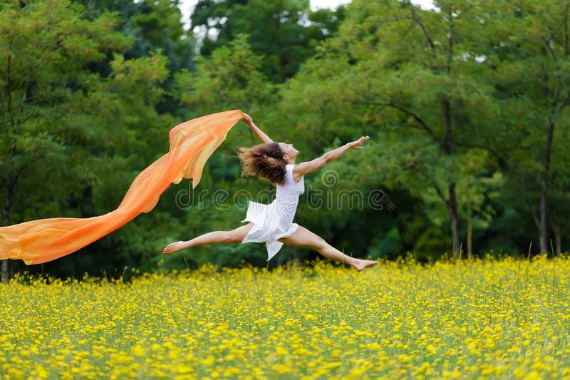 Agile woman leaping in the air. Agile barefoot woman with curly brown hair leaping in the air in a meadow of yellow wildflowers trailing a colorful orange scarf stock image
