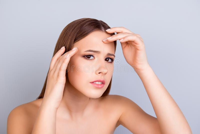 Aging, acne, pimple, wrinkles, oily, dry skin concept. Cose up c. Ropped photo of pretty young lady touching her forehead and look serious and worried stock images
