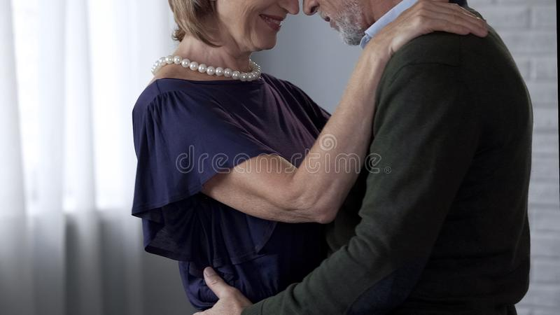 Aging couple dancing and hugging date, lady smiling playfully, loving relations royalty free stock images