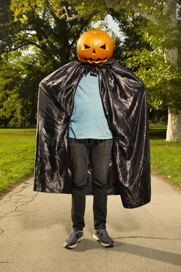 Aging man in city park haunts with pumpkin head royalty free stock photo