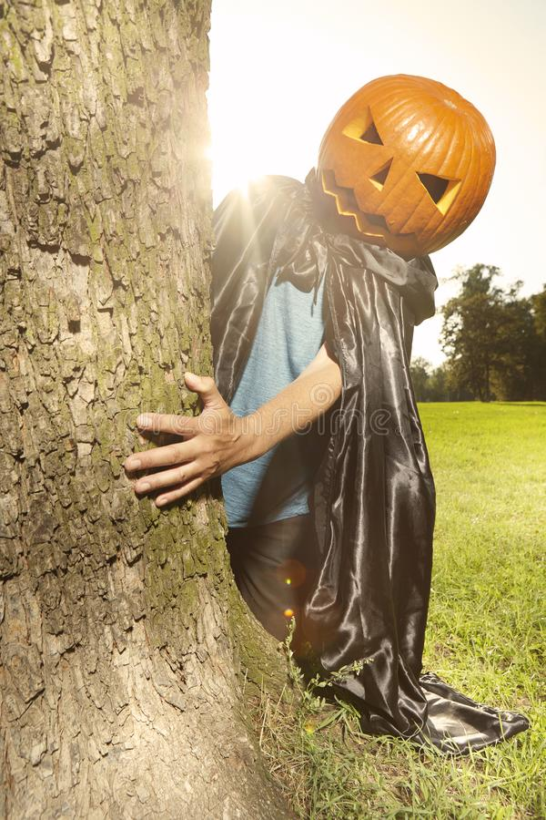 Aging man in city park haunts with pumpkin head. Older man in hooded cloak haunts in city park stock photography