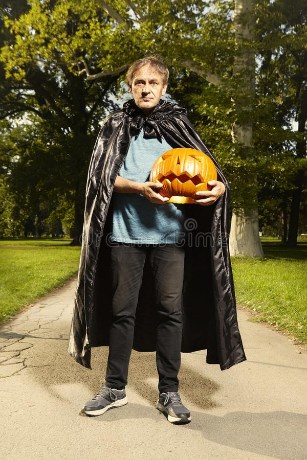 Aging man in city park haunts with pumpkin head. Older man in hooded cloak haunts in city park stock images