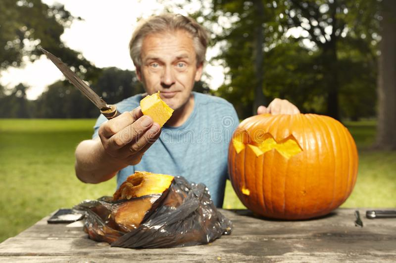 Aging man in city park preparing funny helloween pumpkin stock photo