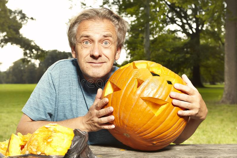 Aging man in city park preparing funny helloween pumpkin stock images