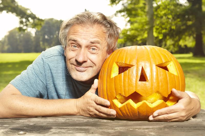 Aging man in city park preparing funny helloween pumpkin stock photography