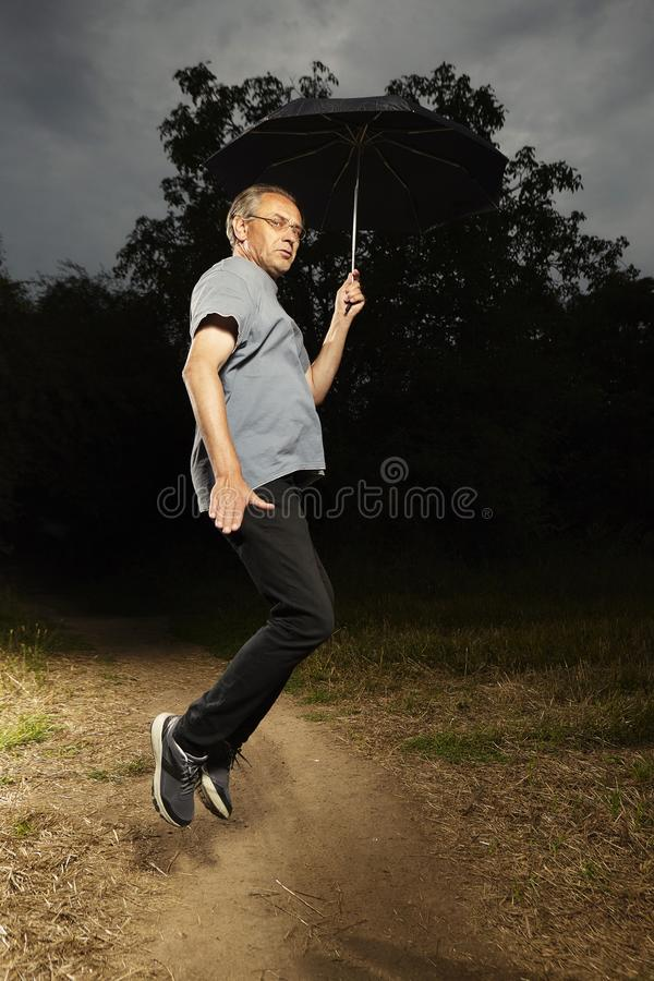 Aging man in hooded shirt jumping on field way with umbrella royalty free stock photography