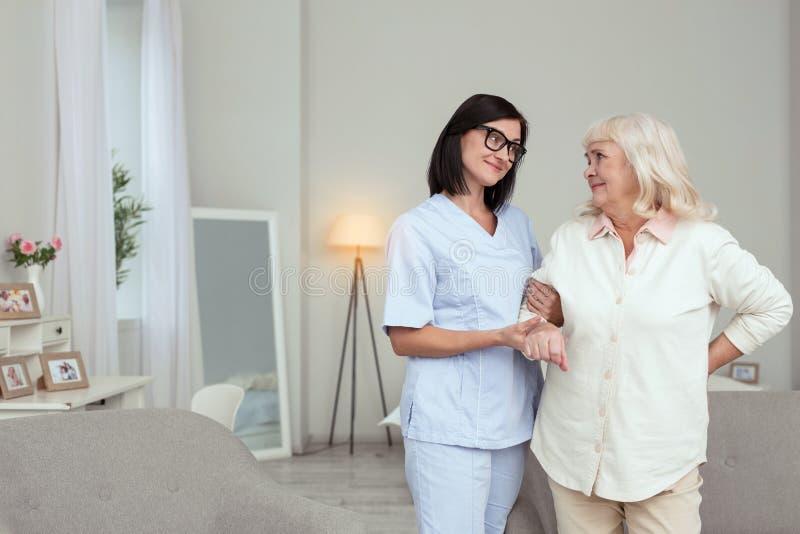 Inspired nurse serving elder woman stock images