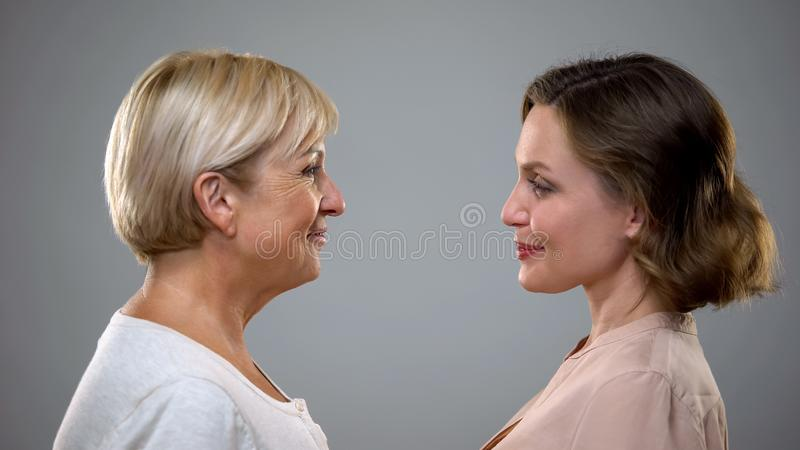 Aging process, adult mum and daughter looking at each other, future reflection royalty free stock image