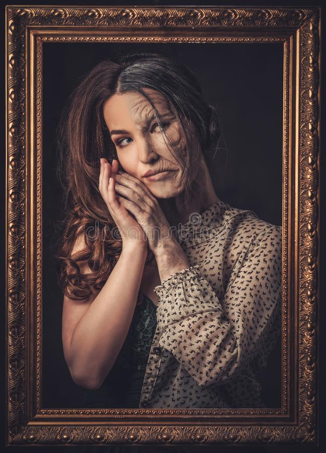 Aging, skin care concept. Half old half young woman with picture frame. stock photo