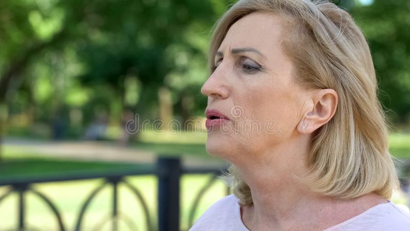 Aging woman doing breathing exercises in park, active lifestyle, healthcare royalty free stock image