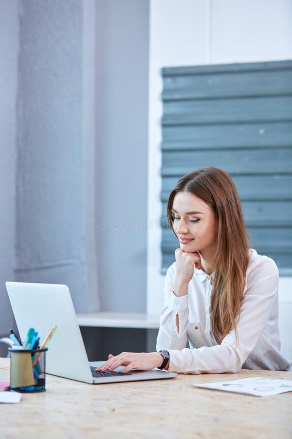 Agirl urzędnik, siedzi przy jej biurkiem i używa laptop fotografia stock