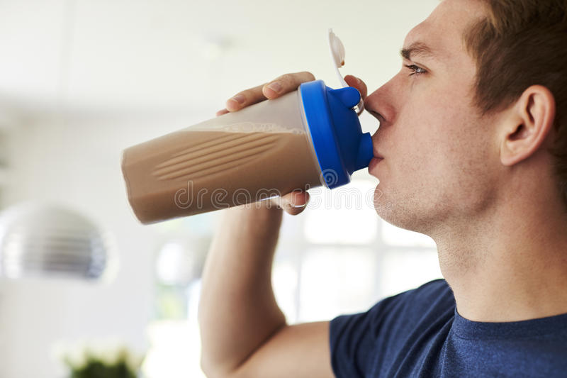 Agitação bebendo da proteína do homem na cozinha em casa fotos de stock royalty free