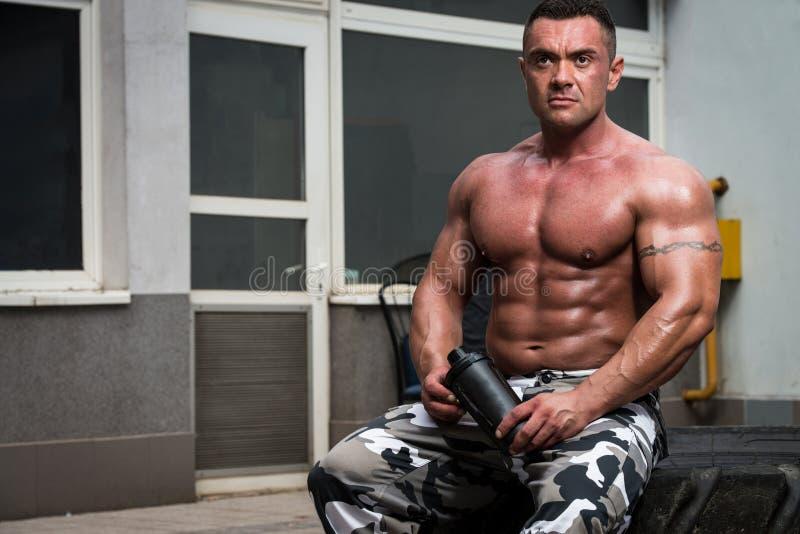 Agitação de descanso e bebendo do halterofilista da proteína após o exercício no gym imagens de stock royalty free