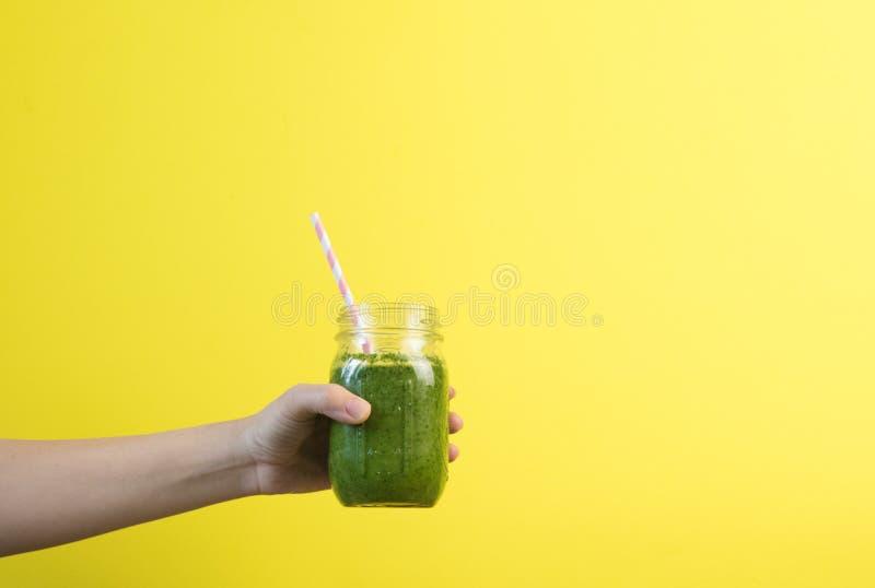 Agitação do batido da terra arrendada da mão da mulher contra a parede colorida Conceito saudável verde bebendo do batido imagem de stock
