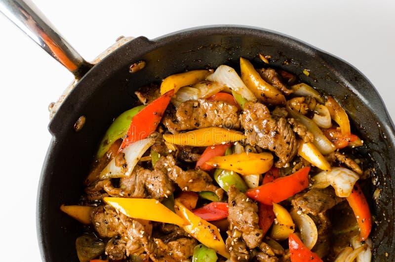 Agitação Fried Beef Steak com pimenta no fundo isolado fotos de stock