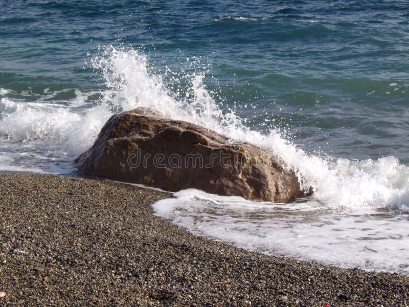 Agita y salpica de la resaca y de la piedra del mar en la costa Piedras y c?scaras en la playa foto de archivo