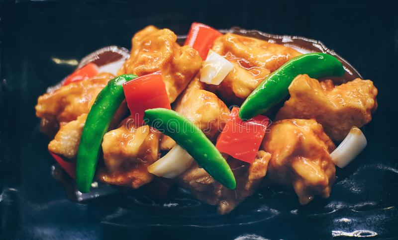 Agitación Fried Pork con los guisantes verdes y la pimienta roja en la placa negra fotos de archivo libres de regalías
