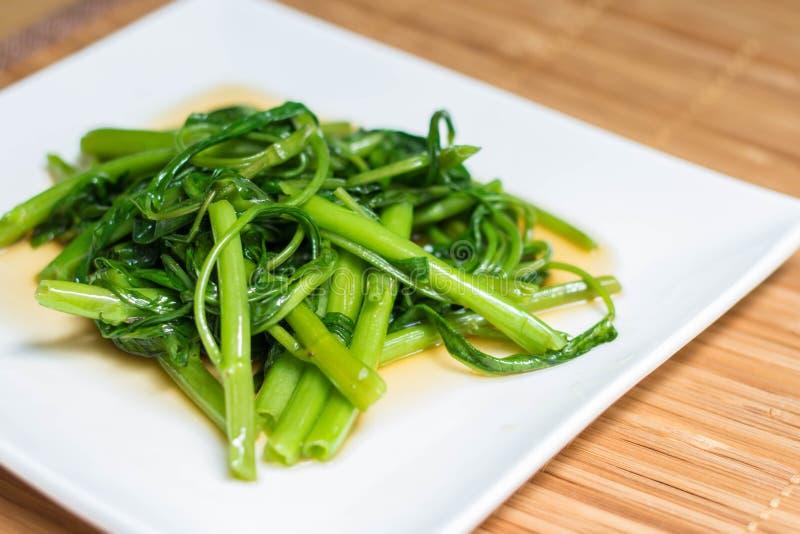 Agitación Fried Water Spinach en la estera de bambú imagen de archivo libre de regalías