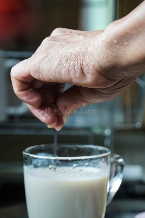 Agitación masculina de la mano al vidrio de leche de soja fotografía de archivo libre de regalías