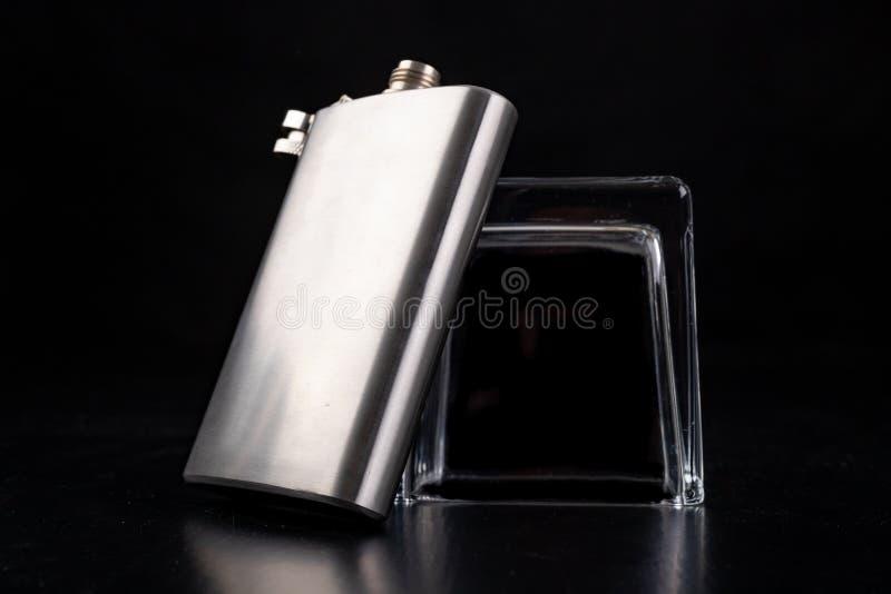 Agitador metálico, frasco de anca e vidro de vodka invertido Acessórios do barman sobre a mesa imagem de stock royalty free