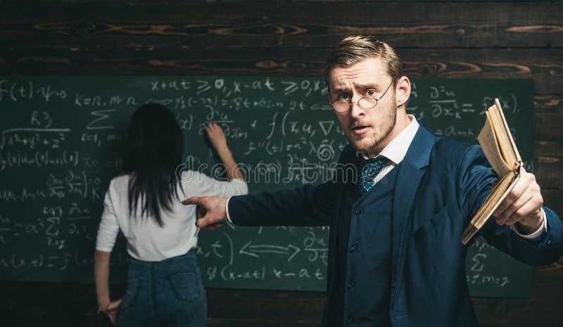Agitated молодой профессор с стильными усиком и бородой указывая книга на студентов в классе пока показывающ формулу стоковые изображения rf
