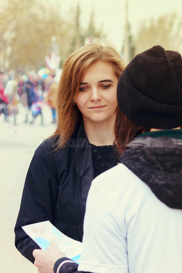 The agitator on the street offers a passer-by to a girl to take a leaflet. Agitation, distribution of material or advertising of. Goods royalty free stock image