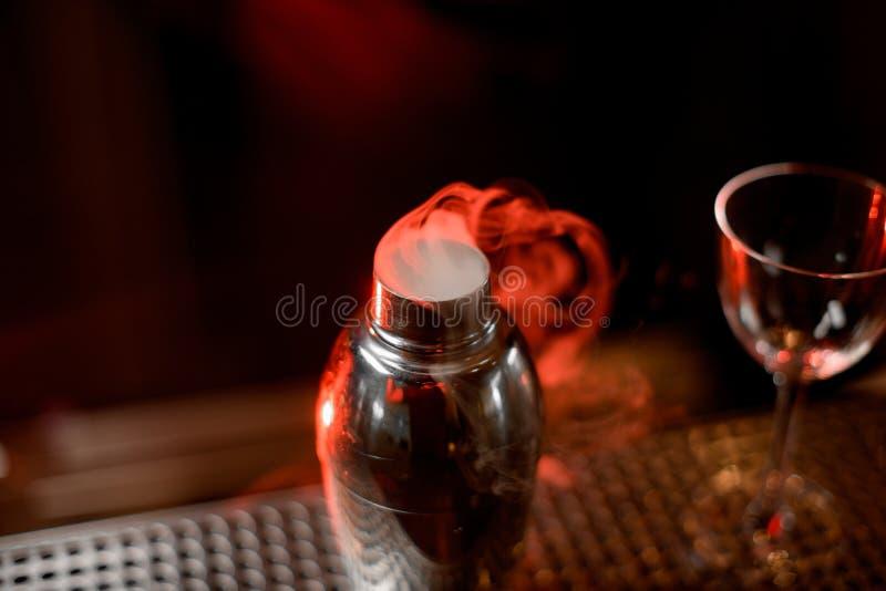 Agitatore con la miscela piena di vapore e vetro sul contatore fotografie stock