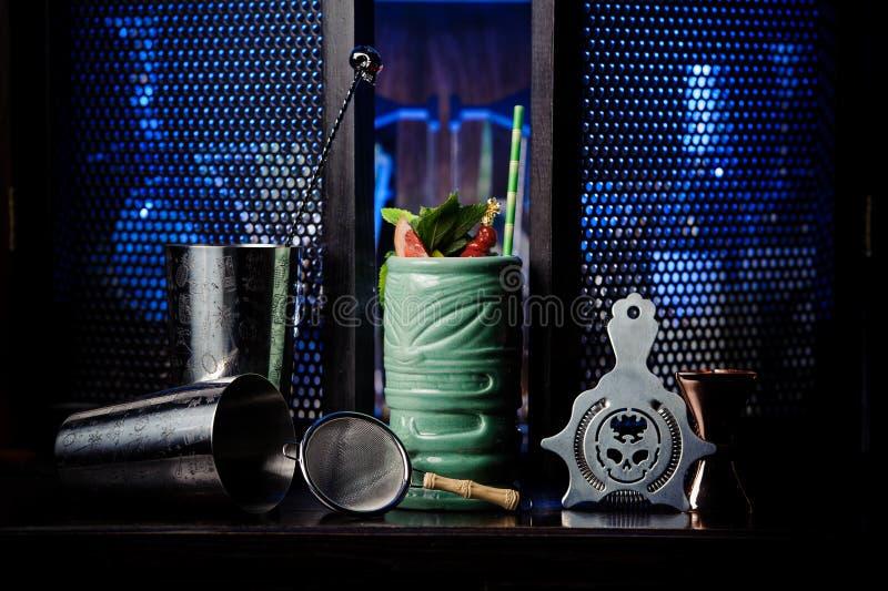 Agitatore d'acciaio vuoto e cocktail tropicale fresco sul davanzale fotografie stock