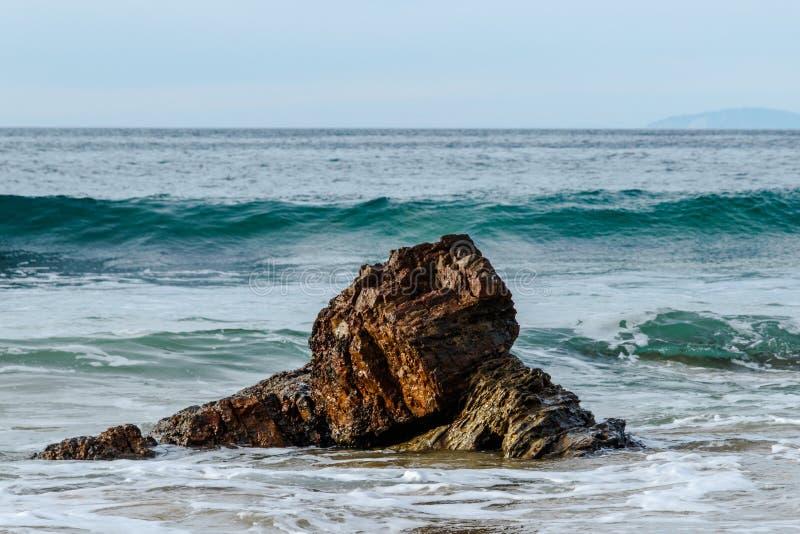 Agite cresting y la mudanza hacia roca cerca de orilla pacífica; espuma en el primero plano, cielo en fondo fotos de archivo