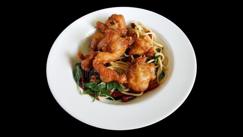 Agite os espaguetes fritados com piment?o secado e o caranguejo macio do escudo, grampeando a parte isolada no fundo preto imagens de stock