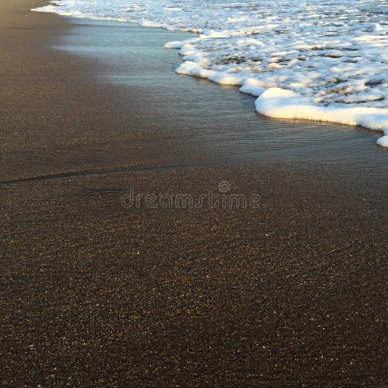 Agite y vare, onda tropical brillante del mar en la arena de la playa en luz de la puesta del sol fotografía de archivo libre de regalías
